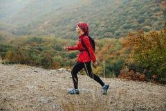 旅行在山行迹步行的女孩游人在雨中 免版税库存照片