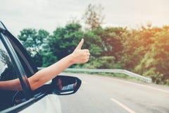 旅行在斜背式的汽车汽车的愉快的美丽的女孩 免版税库存照片