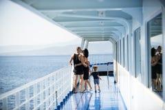 旅行在晴天家庭和爱概念的游轮的家庭 父亲、母亲和孩子在巡航甲板站立  免版税库存图片