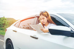 旅行在有地图的一辆斜背式的汽车汽车的愉快的美丽的女孩 免版税库存图片