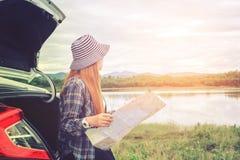 旅行在有地图的一辆斜背式的汽车汽车的愉快的美丽的女孩 免版税库存照片