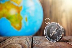 旅行在木背景的指南针和地球globus 旅途,冒险生活方式 回家的路 ?? 库存照片