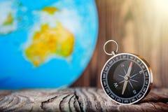 旅行在木背景的指南针和地球globus 旅途,冒险生活方式 回家的路 ?? 免版税库存照片
