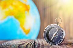 旅行在木背景的指南针和地球globus 旅途,冒险生活方式 回家的路 ?? 免版税图库摄影