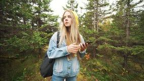 旅行在森林的愉快的旅游可爱的少妇,寻找在导航员的方式在电话 股票录像