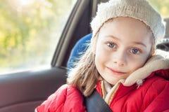 旅行在汽车的愉快的微笑的女孩在秋天期间 免版税库存图片