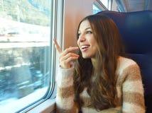 旅行在火车和指向地方的愉快的微笑的妇女通过窗口 免版税库存图片