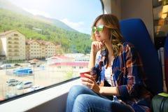 旅行在火车的美丽的女孩 罗莎Khutor 图库摄影
