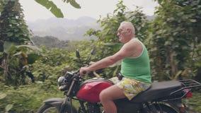 旅行在绿色山风景的摩托车的摩托车骑士人 驾驶在热带高地的老人摩托车 影视素材
