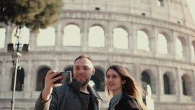 旅行在罗马,意大利的年轻愉快的夫妇 拍在智能手机的男人和妇女selfie照片在罗马斗兽场附近 免版税库存图片
