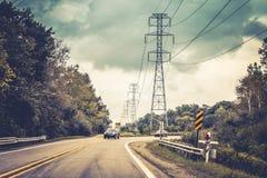 旅行在路的汽车在与一个十字架的一个角落附近在前景一个冷面提示安全地驾驶 免版税图库摄影