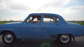 旅行在高速公路的经典老汽车在多雨夏日 驾驶在葡萄酒汽车的乡下公路的年轻夫妇 股票录像