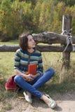 旅行家女孩与书坐自然 免版税库存图片