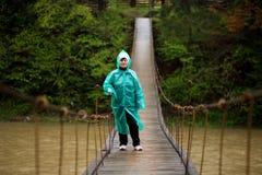 旅行家资深美女在蓝色由取决于的桥梁的雨夹克发怒河在森林里,享受沈默 免版税库存照片