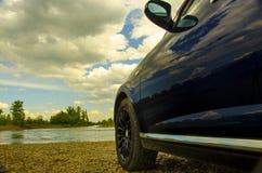 旅行对夏天 在一条乡下公路的汽车在河的背景 库存照片