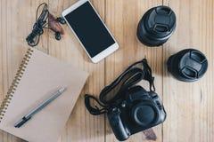 旅行对象顶视图:在棕色笔记本的灰色铅笔 并且白色移动电话、耳机、黑照相机和两透镜在木ta 库存图片