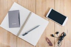 旅行对象顶视图:护照和灰色铅笔在白色笔记本、白色手机和黑耳机在木桌上 图库摄影