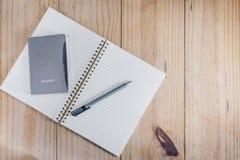 旅行对象顶视图:护照和灰色铅笔在白色笔记本和木桌 库存照片