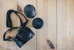 旅行对象顶视图:黑照相机和两透镜在木桌上 免版税库存图片