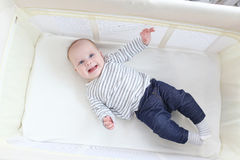 旅行小儿床的微笑的愉快的3个月女孩 免版税库存图片