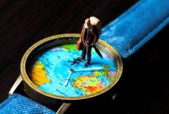 旅行手表的老人 世界地图旅行照片横幅 年迈的旅客小雕象 库存照片
