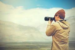 旅行摄影师新闻工作者在山背景中的拿着一台dslr照相机 库存图片