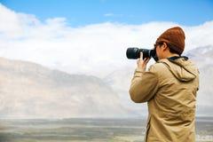 旅行摄影师新闻工作者在山背景中的拿着一台dslr照相机 免版税库存照片