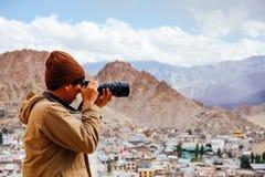 旅行摄影师新闻工作者特写镜头在山背景中的拿着一台dslr照相机 库存照片