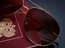 旅行旅游业概念在灰色背景梯度的太阳镜护照 免版税库存图片