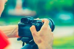 旅行有照相机的背包徒步旅行者摄影师在自然背景在手中做照片 库存照片