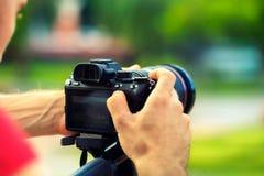 旅行有照相机的背包徒步旅行者摄影师在自然背景在手中做照片 库存图片