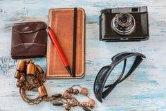 旅行概念,与老照相机、钱包、书、笔和玻璃 免版税库存图片