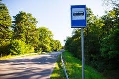 旅行概念-在森林公路的公共汽车站 图库摄影