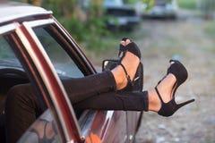 旅行概念 妇女垂悬她的腿在汽车的窗口外面 免版税库存照片