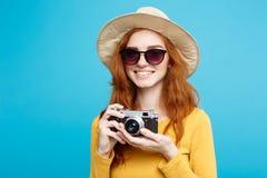 旅行概念-接近的有时髦帽子、sunglass和葡萄酒照相机的画象年轻美丽的可爱的redhair女孩 库存图片