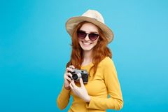 旅行概念-接近的有时髦帽子、sunglass和葡萄酒照相机的画象年轻美丽的可爱的redhair女孩 免版税库存照片