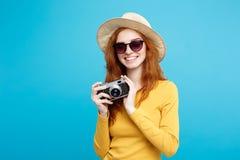旅行概念-接近的有时髦帽子、sunglass和葡萄酒照相机的画象年轻美丽的可爱的redhair女孩 图库摄影