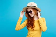 旅行概念-接近的有时髦帽子和sunglass微笑的画象年轻美丽的可爱的redhair女孩 蓝色 库存图片