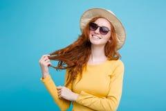 旅行概念-接近的有时髦帽子和sunglass微笑的画象年轻美丽的可爱的redhair女孩 蓝色 图库摄影