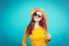 旅行概念-接近的有时髦帽子和sunglass微笑的画象年轻美丽的可爱的redhair女孩 蓝色 免版税库存照片
