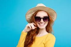 旅行概念-接近的有时髦帽子和sunglass微笑的画象年轻美丽的有吸引力的姜红色头发女孩 图库摄影