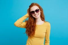旅行概念-接近的有时髦sunglass微笑的画象年轻美丽的有吸引力的姜红色头发女孩 蓝色 库存照片