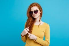 旅行概念-接近的有时髦sunglass微笑的画象年轻美丽的有吸引力的姜红色头发女孩 蓝色 库存图片