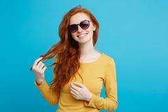 旅行概念-接近的有时髦sunglass微笑的画象年轻美丽的有吸引力的姜红色头发女孩 蓝色 免版税库存照片