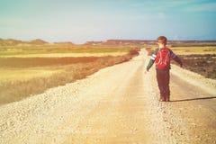 旅行概念-步行在路的小男孩对山 免版税库存照片