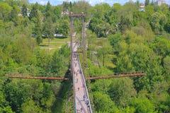 旅行横跨桥梁的人剪影  图库摄影
