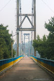 旅行横跨桥梁的人剪影  免版税库存照片