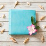 旅行照片的家庭蓝色象册从环境皮革和贝壳在木板 顶视图 免版税库存照片