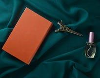 旅行爱的概念向法国 书,艾菲尔铁塔的小雕象,一个瓶在黑暗的板料的香水 顶视图 免版税库存照片