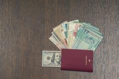 旅行生物统计的护照特写镜头与一一百美元里面和捆绑的在桃花心木桌上的亚洲金钱 库存照片